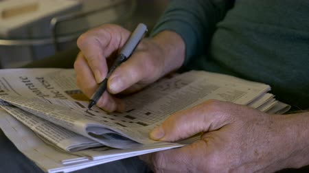 idade média : Hand held of an elderly man filling out a crossword puzzle with a pen from a newspaper Stock Footage