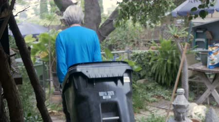 hajápoló : An active elderly senior wheels an empty trash can into his yard getting ready for some yard work, or clean up Stock mozgókép