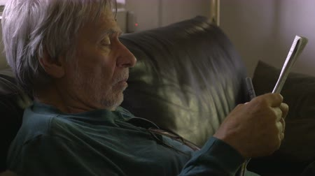 cidadão idoso : A healthy senior with good vision reads a newspaper on his sofa with a pen in his hand dolly shot