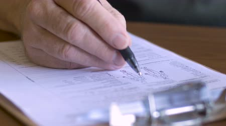 healthy office : An elderly man fills out a medical form on a clipboard - close up dolly shot Stock Footage