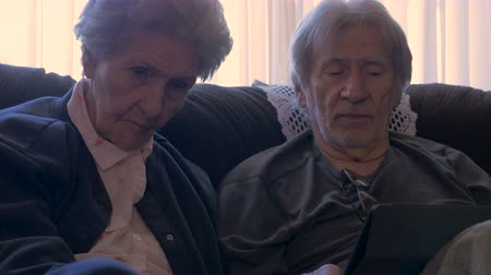 запомнить : An elderly man in his 70s explains to an older woman in her 90s details about using a tablet in 4k