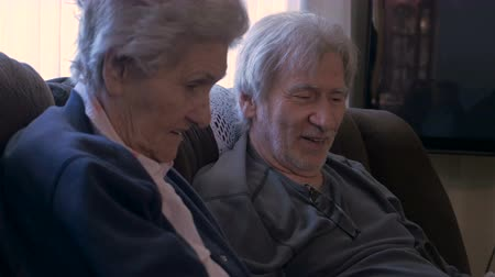 запомнить : Hand held of an elderly son in his 70s and his older mother in her 90s laughing, talking, and looking at a mobile tablet on a couch in 4k