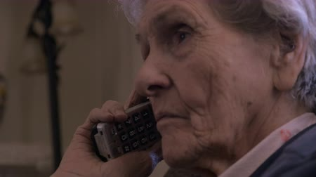 hatırlamak : A 90 year old woman listens carefully to a phone conversation on a cordless telephone close up. She appears serious and maybe talking to a doctor, pharmacist, or other health care professional. Stok Video