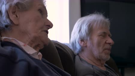 falar : A mother and son both in their golden years talking with each other on a sofa in 4k