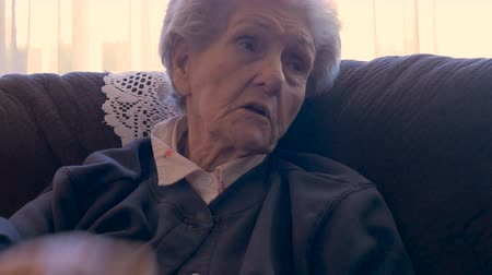 запомнить : An elderly woman in her 90s, sitting on a sofa, talking and using her hands for emphasis in 4k