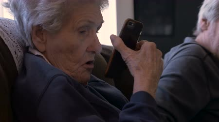 интимный : An elderly man shows a smart phone to an older woman in her 90s who has trouble seeing the screen. Стоковые видеозаписи
