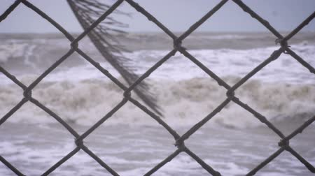 давление : Slow motion rack focus on a chain link fence and a heavy surf from a storm on the ocean representing rising sea levels, climate change, and loss of beach front property Стоковые видеозаписи