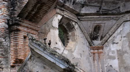 abandonar : Medium shot pan of a church destroyed in an earthquake in Antigua, Guatemala showing some of the prior attempts at rebuilding in this seismically active zone