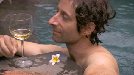 na zdraví : Middle aged man swims up to a glass of white wine while in a swimming pool and takes a drink with a tropical flower on the edge. Dostupné videozáznamy