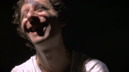 bipolar disorder : Mentally ill man laughing in dramatic lighting. He appears crazy or disturbed. He has a maniacal laugh.