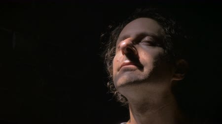 mężczyźni : A middle aged man looks up towards the sky for resolve and answers in the dark while closing his eyes. It looks like he gets relief and what he is looking for.