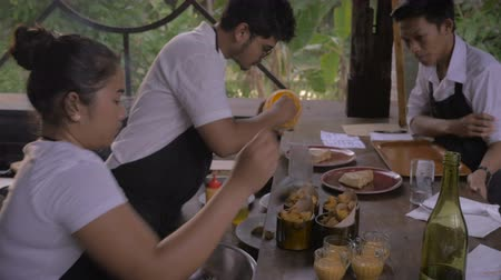 grilling : Two chefs serve food while a waiter confirms an order at an outdoor restaurant or cafe. The woman is serving potatoes and the man is adding an orange sauce to an omelet, or Spanish tortilla
