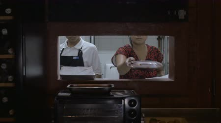 bandeja : Four people work together in a busy kitchen. We see three people through a window to the back of the kitchen where everyone cooperates together to get their job done. Stock Footage