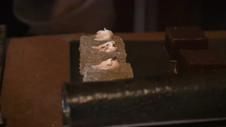 cozinhar : A close up dolly shot of a hand applying sprinkles to a dessert