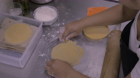decadência : A pastry chef uses a mold to create a round piece of dough and then lifts it off the stainless steel table with a plastic spatula