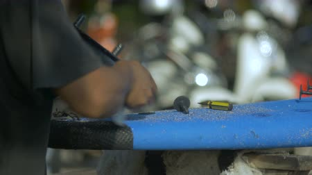 substituição : A man replaces the fin on a surfboard that has sand on its surface - hand held with shallow depth of field