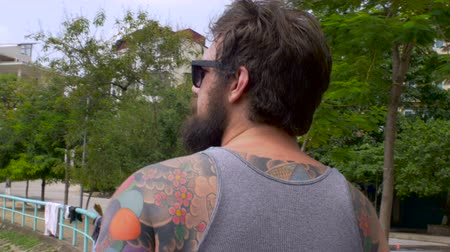 significar : A young hipster man with a full beard and colorful full back tattoos turns his back to the camera, drinks a beer, and walks away as the camera follows him outside along a lake in the summer.