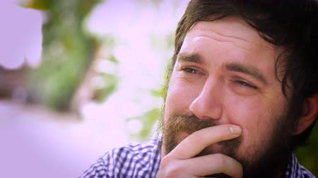 be sad : Close up portrait of a young hipster man with a full beard who is severely depressed and sad. He is holding back tears and could even be suicidal. A real life emoticon in an outdoor setting with natural lighting and a unique expression. Stock Footage