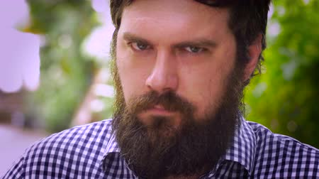 lét : Close up portrait of a young hipster man with a full beard quietly being pissed off, angry, or mad. He is holding in his emotions and breathing hard to stay composed but you can see how upset he is. A real life emoticon in an outdoor setting with natural
