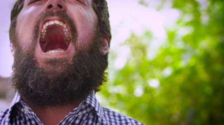 sinir : Dolly shot close up portrait of a young hipster man with a full beard screaming out loud in anger. He is visibly pissed off and potentially dangerous. A real life emoticon in an outdoor setting with natural lighting and a unique expression. Stok Video