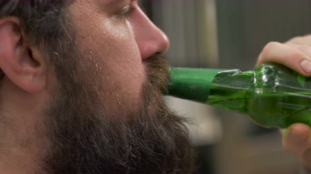 pažba : Hand held close up portrait of a young hipster man with a full beard drinking a beer out of a green bottle outside in natural lighting.