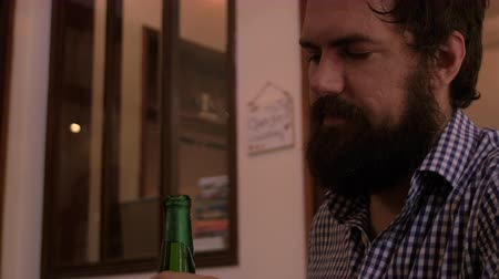 алкоголизм : Hipster with a full beard orders a beer and takes a drink as the bartender opens the bottle for him.