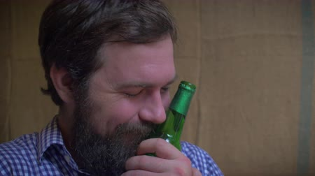 não alcoólica : Close up portrait of a young hipster man with a full beard who is in love with his beer. He kisses it, hugs it, and holds the beer bottle close to him like a person. A real life emoticon. Stock Footage