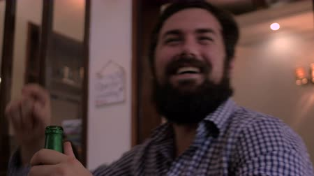 żart : Close up of a young hipster man with a full beard drinking a beer at a bar and then laughing at someone telling him a good joke. He slaps his knee and laughs very hard. Wideo