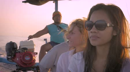 be sad : Slow motion of three tourists on a sightseeing boat tour in Bali in the morning sun. One of the tourists is having a great time, while the other appears to be distracted and sad.