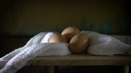 emekli olmak : Dolly shot of three eggs with droplets of moisture on the shells and a cotton cloth on a wooden cutting board resembling an oil still life painting from the renaissance period. Stok Video