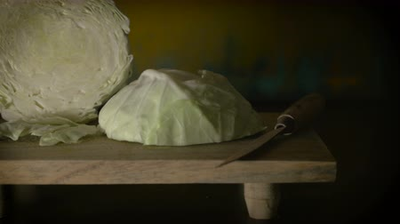 salata : Dolly shot of green cabbage arranged on a wooden cutting board like a renaissance still life oil painting