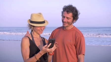 paylaşımı : Two thin and fit tourists look at photos of themselves while standing on the beach. The middle aged athletic man and younger woman share moments with each other. Handheld.