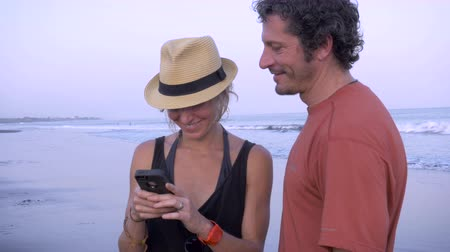 conectado : Hand held shot of an attractive, athletic couple sharing a moment together with their phone on the beach. The middle aged man has embraced her phubbing behavior.