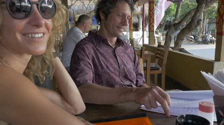 burmak : A young, thin, blond woman twirls her hair while a man looks over a menu in an outdoor cafe or restaurant in a warm tropical setting.