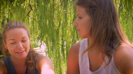 интимный : Medium close up dolly shot of two young attractive girlfriends talking to one another in a serious and personal conversation while sitting outside under a tree by a water pond or lake on a bright summer day.
