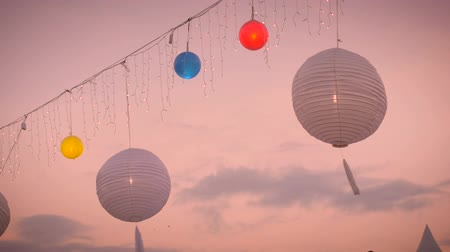 lampy : White and colored lanterns blow gently in the breeze against the colored sky at sunrise or sunset with christmas lights gently swaying in the wind. Dostupné videozáznamy