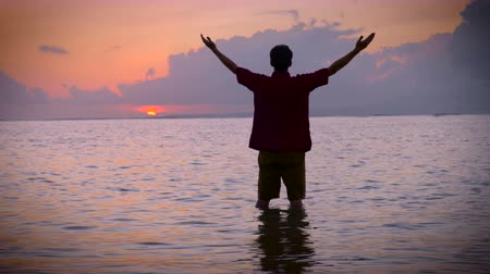 duše : Tilt up shot of a man moving his arms into a worship pose while standing in the water on a beach reaching out towards the sun seeking answers and looking for inspiration at sunrise or sunset. Dostupné videozáznamy