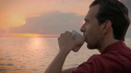 kahve molası : Side profile view of a middle aged man enjoying a cup of coffee as he watches the sunrise over the ocean. A perfect way to start any morning relaxing, and thinking about the great things in store for the day.