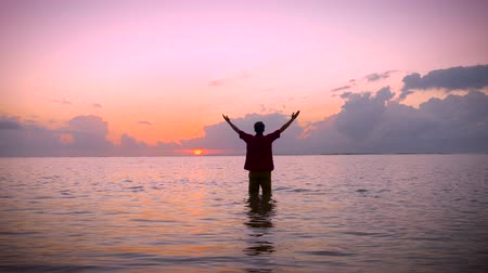 ibadet : Man standing still in a calm ocean, raises his arms towards the sun in the early morning sunrise to a worship pose while looking up at the sky seeking answers and looking for inspiration.