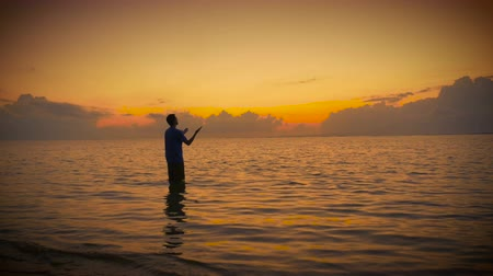 duše : Man in prayer opens his hands to the sun and sky to receive the good grace of the lord while standing in a calm ocean at sunrise or sunset.