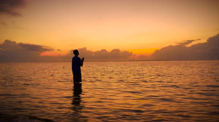 дух : Man worships with his head up to the sky and his hands together praying while standing still in the ocean during sunrise or sunset seeking the truth from a higher power, God, the Universe, or the holy spirit. Стоковые видеозаписи