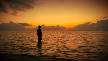 duše : Wide slow push in of solo man stands in stillness of the ocean looking up towards the sky in prayer surrounded by colorful and bright early morning sunrise or sunset. Bowing and raising his head to the sky to a higher power of love, God, and the world.