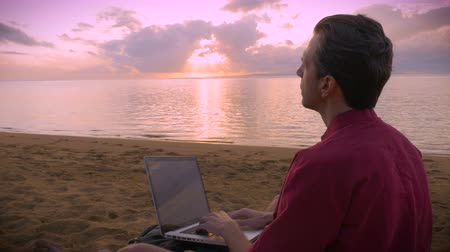 teclado : A middle aged man working on the beach during a sunrise or sunset pauses to take in how amazing his life is.