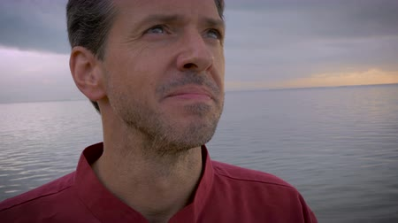 emekli : A middle aged man smiles and looks inspired by life overlooking the beach during sunrise or sunset on his early retirement. He is healthy, his family is well and everything in his life is perfect. Stok Video