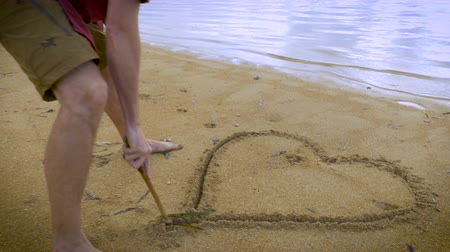 öneri : Attractive man in casual red shirt draws a heart in the sand with a stick on a beautiful tropical vacation beach.