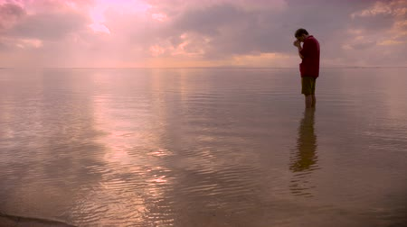 náboženství : Side view of a man standing in a calm ocean or lake while he bows his head in prayer asking for inspiration, answers, salvation, or solutions to his problems at sunset or sunrise. Dostupné videozáznamy