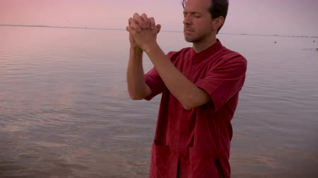 освещенный : Hand held shot of middle aged man in red shirt closing his eyes, putting his hands together in prayer, looking up to the sky while standing in a calm lake or ocean. Стоковые видеозаписи