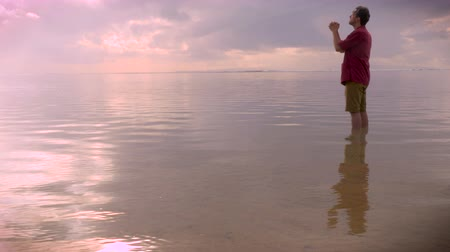 duše : A middle aged man praying while standing in an ocean with crashing waves in the far distance during sunrise or sunset, side view hand held.
