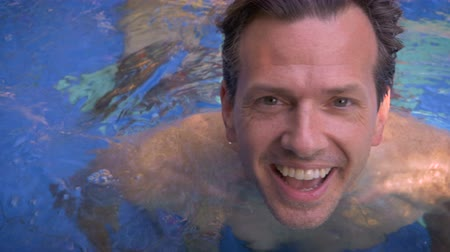 treading : Close up portrait of a younger and active middle aged active man or father in a pool swimming up to the camera smiling.