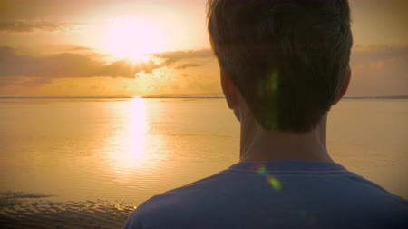 gondolkodás : Hand held over the shoulder shot of a man watching a sunset or sunrise over a calm ocean or lake while the sun reflects off the water.